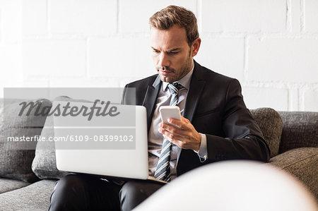 Focused businessman using laptop and smartphone