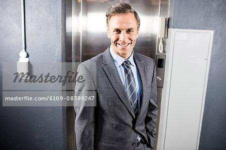 Smiling businessman standing front of elevator
