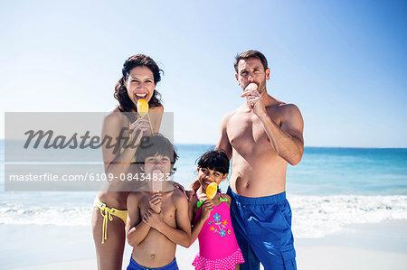 Cute family eating ice creams on the beach