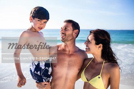 Cute couple carrying their son on the beach