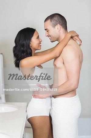 Smiling Couple In Underwear Hugging Bathroom