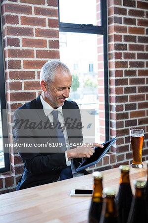 Businessman using tablet in a pub