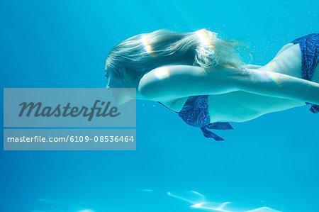 Smiling woman swimming underwater