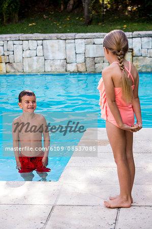 Siblings standing at swimming pool