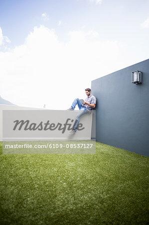 Man sitting on terrace using digital tablet