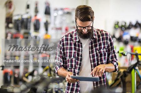 Bike mechanic checking a tablet computer