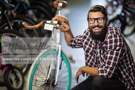 Bike mechanic crouching next to a bicycle