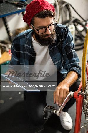 Bike mechanic looking at tablet computer