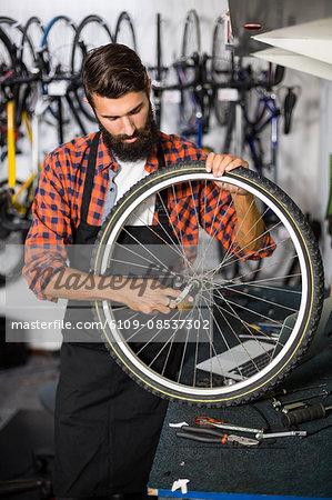 Hipster bike mechanic holding a bike wheel