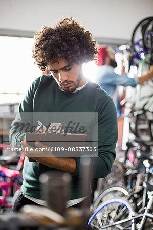 Hipster bike mechanic writing on clipboard