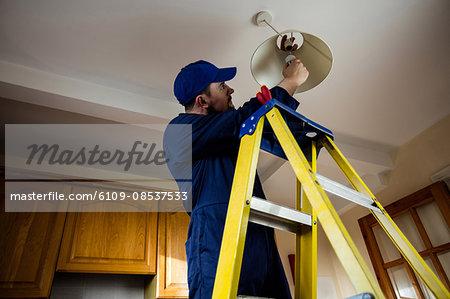 Electrician repairing a ceiling lamp