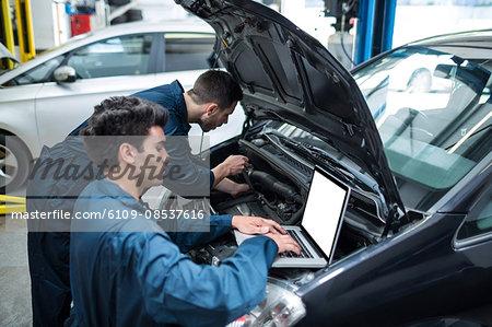 Mechanics examining car engine using laptop
