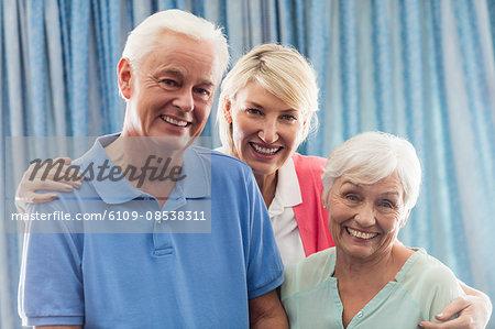 Nurse hugging a senior couple