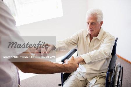 Nurse helping senior man to stand up