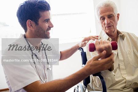Nurse helping senior man with doing exercises