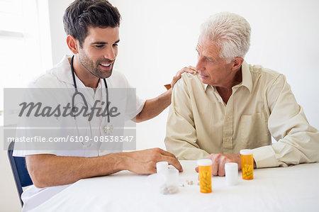 Nurse giving medicine to senior man