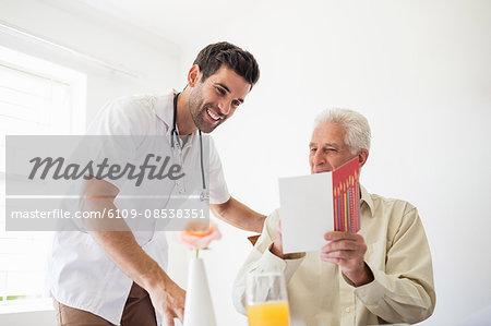 Senior man showing a birthday card the the nurse