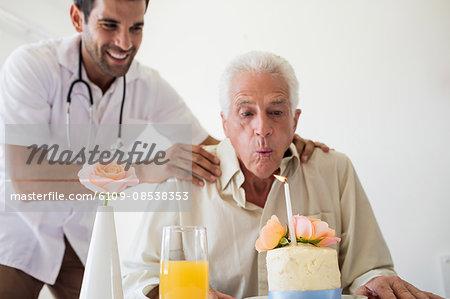 Senior man celebrating his birthday with a cake
