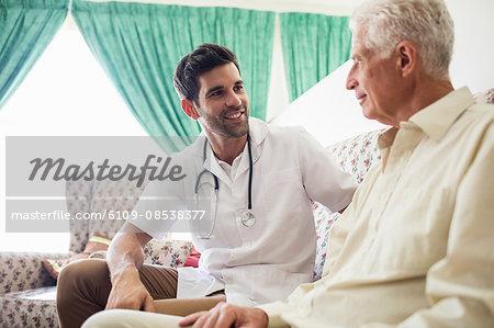 Nurse and senior man sitting on sofa
