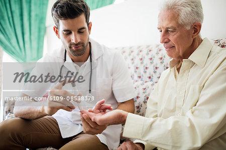 Nurse testing blood glucose of a senior man