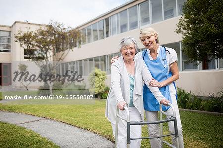 Nurse helping senior woman walking