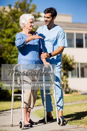 Nurse pushing the senior womans Zimmer frame