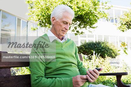 Senior man texting someone