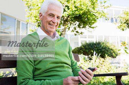Senior man posing with his smartphone
