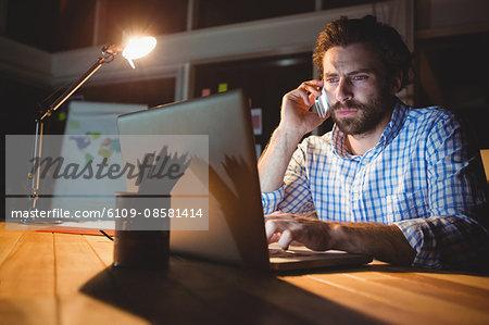 Businessman making a phone call at night