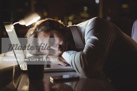 Businessman sleeping on his laptop at night