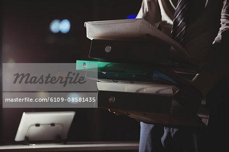 Businessman carrying folder at night