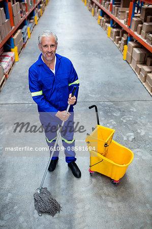 Smiling man moping warehouse floor