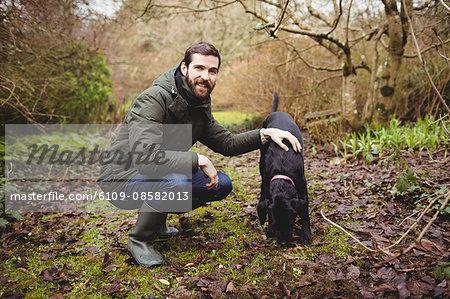 Hipster man smiling at camera while stroking his dog