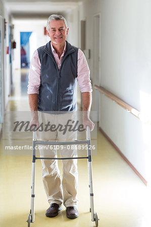 Portrait of senior man standing in hospital corridor with walking frame