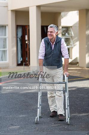 Senior man walking with a walking frame outside the hospital