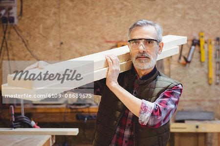 Portrait of a carpenter holding wood plank on his shoulder in a workshop
