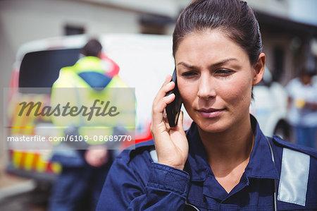 Portrait of a serious ambulance women making a phone call - Stock