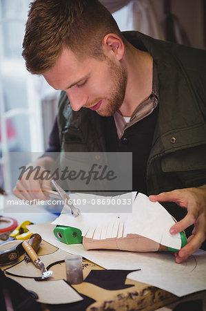 Cobbler hammering nail on shoemaker in workshop