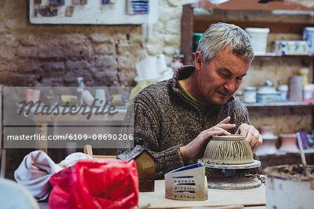 Focsed male potter working at workshop