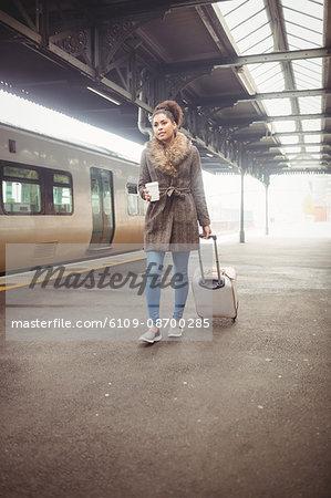 Woman carrying luggage while walking at railroad station platform