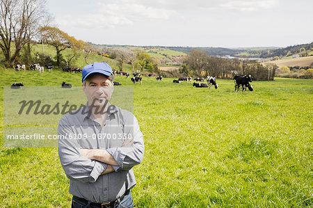 Portrait of confident farmer standing on grassy field