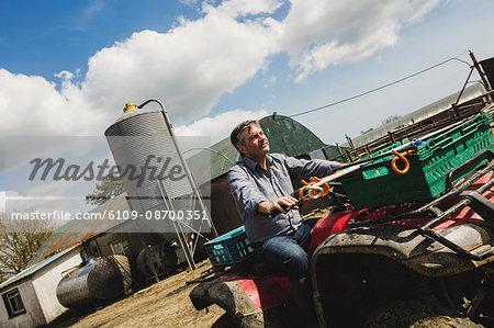 Tilt image of farmer riding quadbike at field against sky