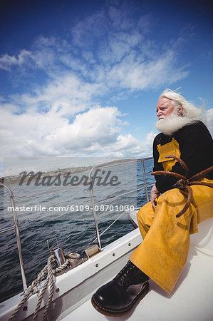 Thoughtful fisherman sitting on fishing boat