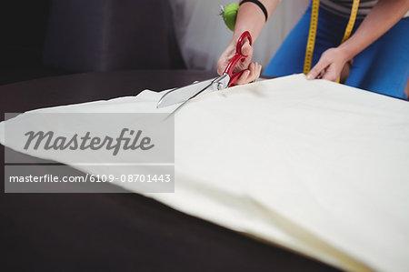 Female fashion designer cutting a white fabric in the studio