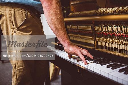 Piano technician repairing the piano at workshop