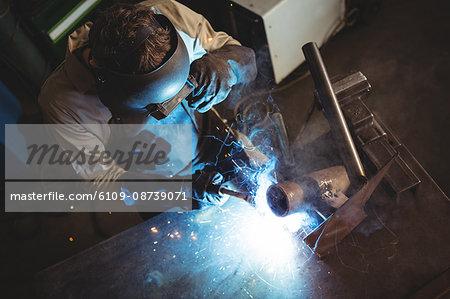 Welder welding a metal in workshop