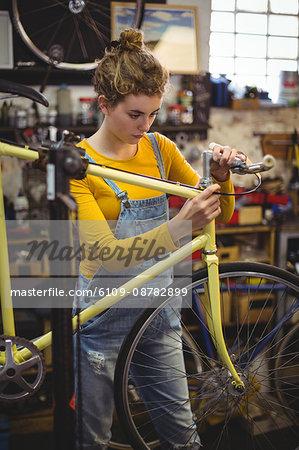 Mechanic repairing a bicycle handle bar in bicycle workshop