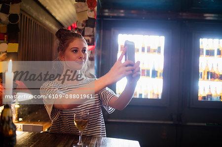 Beautiful woman taking selfie from mobile phone in bar