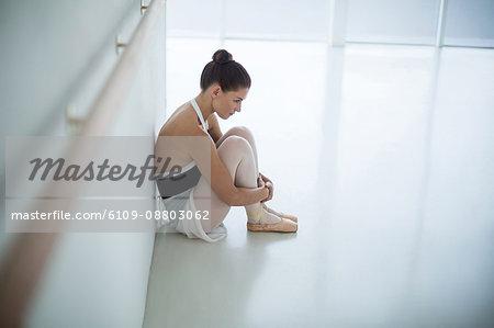 Sad ballerina sitting on floor in the ballet studio