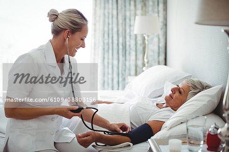 Nurse checking blood pressure of senior woman at home